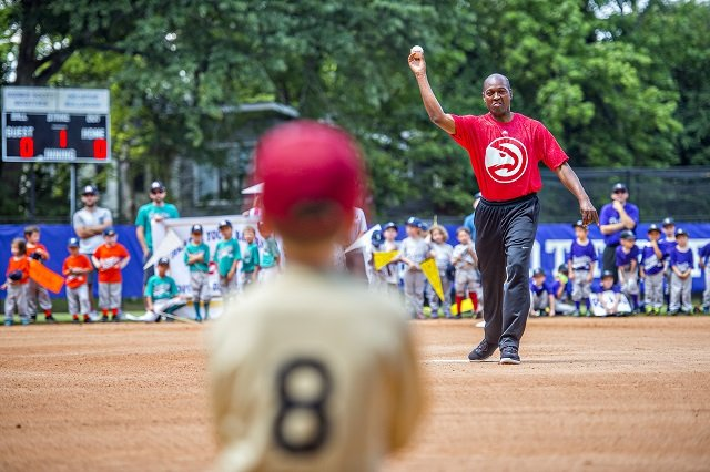 Mike Glenn (right), a former Atlanta Hawks player, throws out the opening pitch during the ceremony for the opening day of Decatur Youth Baseball at Oakhurst Park. File Photo: Jonathan Phillips