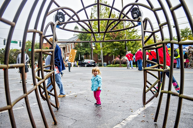 Addison Diethorn (center) walks through a fish skeleton made from metal during the Atlanta Maker Faire in Decatur on Saturday. Photo: Jonathan Phillips