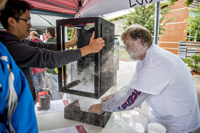 Phillip Wu (left) helps Alan Davies with his vortex machine as he sets in a tub of dry ice during the Atlanta Maker Faire in Decatur on Saturday. Photo: Jonathan Phillips