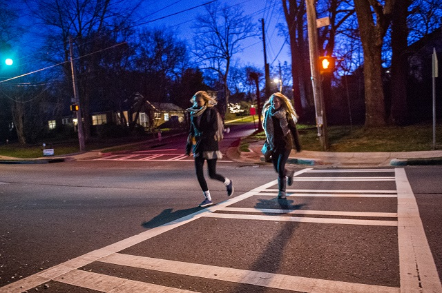Sydney Balcom (left) and Sophia Aiken cross S. Candler St. at Kirk Rd. on their way to school on Wednesday morning. Photo: Jonathan Phillips
