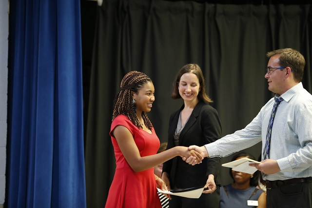Photo Caption: Jaz'Min McKeel receives her certificate from Teacher Peter Robertson while Museum School Principal Katherine Kelbaugh looks on during a ceremony May 26, 2016, celebrating the advancement of the school's first 8th grade class. Photo provided by the Museum School.