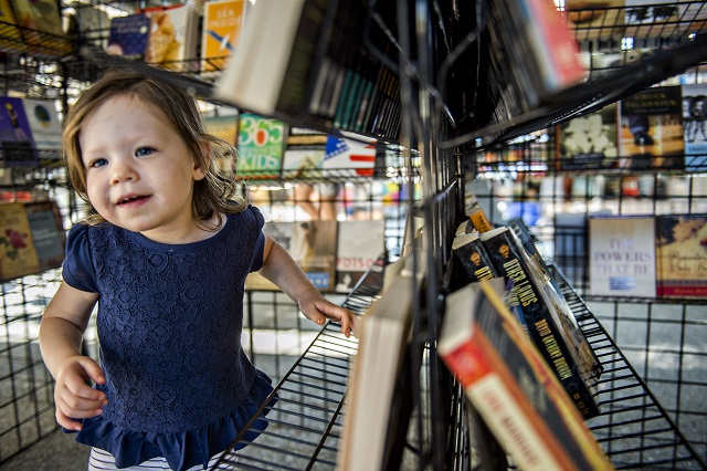 Sabina Uroic plays amongst racks of books during the Decatur Book Festival on Saturday. Photo: Jonathan Phillips