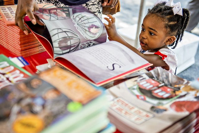 "Zendaya Richards flips through the pictures of ""The Adventures of Amelia, the Crazy Jumping Hedgehog"" during the Decatur Book Festival on Saturday. Photo: Jonathan Phillips"