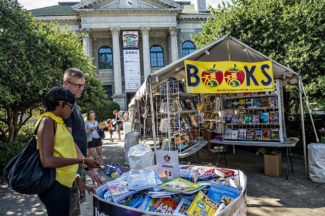 Irene Muturi (left) and Chris Andrews check out some of the books for sale during the Decatur Book Festival on Saturday. Photo: Jonathan Phillips
