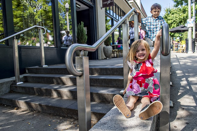 Josie Vance and Declan Llewellyn slide between the handrails as they wait to cross Church St. to get to the children's section of the Decatur Book Festival on Saturday. Photo: Jonathan Phillips