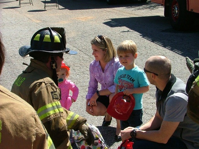 A DeKalb fireman talks to a family about fire safety. Photo provided by DeKalb County Fire Rescue